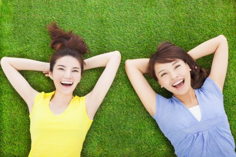 two smiling young woman lying on meadow in park